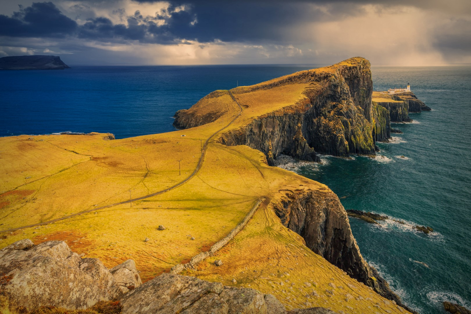 Dramatic cloudy and rainy sky over Neist Point and its lighthouse on Isle of Skye, Scotland, UK